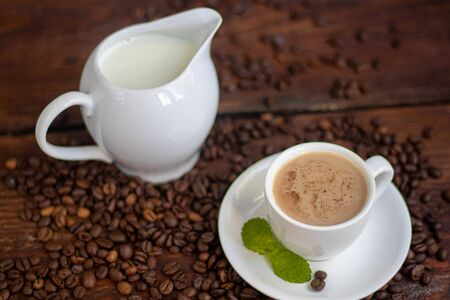 Cup of coffee on a dark background. White milkman. Milk is pouring from it into a cup. On a saucer there are mint leaves, brown grains are scattered nearby,