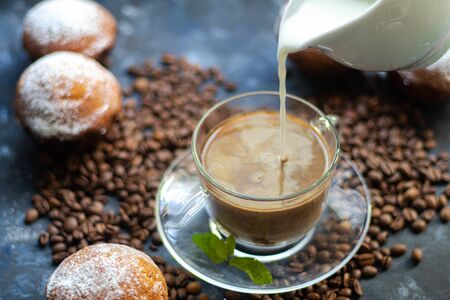 Cup of coffee on a dark background. White milkman. Milk is pouring from it into a cup. On a saucer there are mint leaves, brown grains are scattered nearby