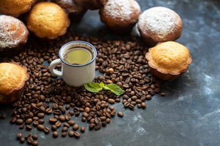 Cup of coffee on a dark background. Brown grains are scattered around the cup, and home-made cupcakes Reklamní fotografie