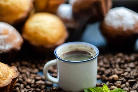 Cup of coffee on a dark background. Brown grains are scattered around the cup, and home-made cupcakes. Reklamní fotografie