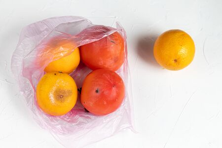 Environmentally harmful packages, spoiled fruits that lie in them. Ugly food. Copy space. Light background.