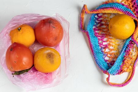 Environmentally harmful packages, spoiled fruits that lie in them. Ugly food. Colored, cotton mesh for fresh produce. Copy space. Light background.