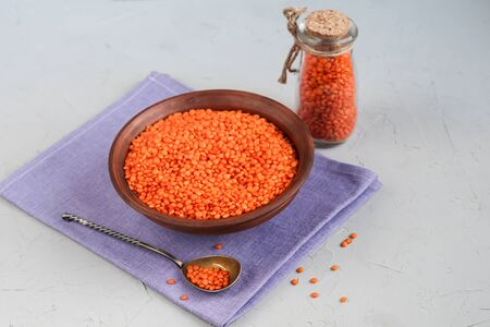 Red lentils in a plate and in a metal spoon on a background under concrete. Ideal food for vegetarians.