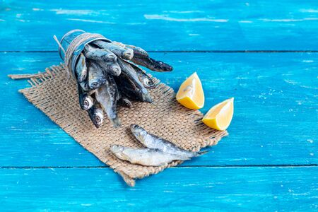 Small, salted fish. Near the slices of lemon. Good snack for beer. Sea fish. Copy space. Background tinted in classic modern blue 2020.