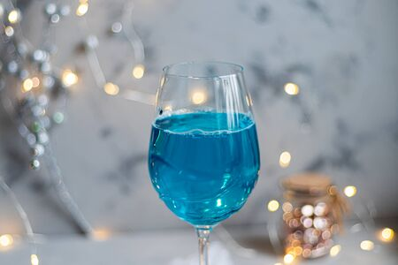 Blue wine in glasses with ice and perspiration on a light background. In the background bokeh of lights. Holiday mood. New Year. Copy space. Stock Photo