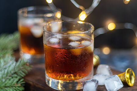 Whiskey in glasses with ice and perspiration on a dark background. A row of tangerines. Festive mood. New Year Christmas. Copy space.