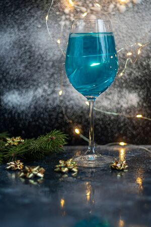 Blue wine in a glass on a dark background. In the background bokeh of lights. Festive mood. New Year. Copy space.