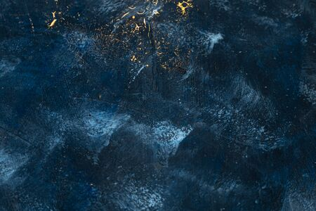 Deep blue with gold splashes over concrete. Copy space.