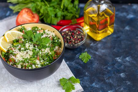 Tabule salad in a round plate on a dark blue background. Couscous, parsley with green onions and tomatoes and mint. Dressed with olive oil and lemon juice. Copy space.