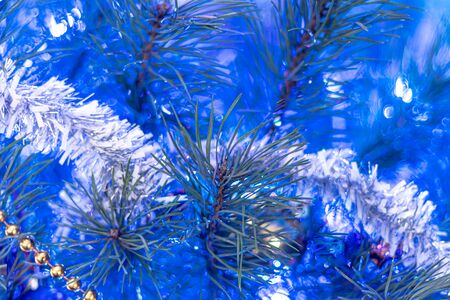 Christmas tree decorated with toys and sparkles. Against the background of blue, trend 2020. The background is blurred, bokeh. Copy space. Stockfoto