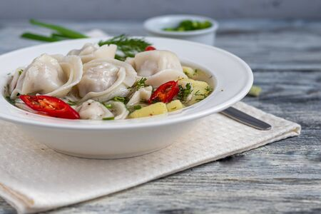 Soup with dumplings garnished with onions and peppers. In the background are greens, red peppers and bay leaves. On a light wooden background. Copy space. Stock Photo