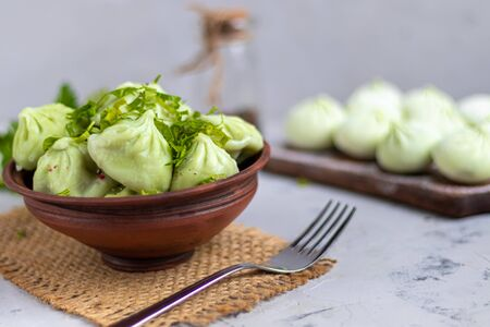 Boiled khinkali made of dough with spinach. Garnished with Red Chilli, Dill and Parsley. On a light gray background under. Raw khinkali frozen on a wooden board next to it. Copy space. Reklamní fotografie - 137799218