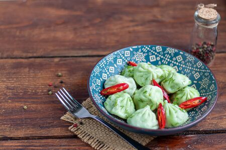 Boiled khinkali made of dough with spinach. Garnished with Red Chilli, Dill and Parsley. On a wooden background. Nearby on a brown board are raw khinkali frozen. Copy space.