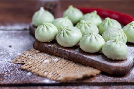 Frozen dough khinkali with spinach. Garnished with Red Chilli, Dill and Parsley. On a wooden background. Copy space.