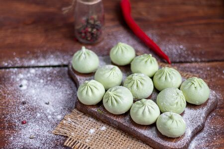 Frozen dough khinkali with spinach. Garnished with Red Chilli, Dill and Parsley. On a wooden background. Copy space. Reklamní fotografie - 137799227