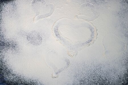 Flour is sprinkled on the table. They draw a heart on it with a finger. Valentines Day. Dark marbled background. White flour.