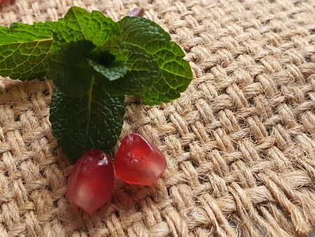 On a burlap are pomegranate seeds closeup and a sprig of mint. Macro shot. Healthy eating Vitamin juice. Copy space.