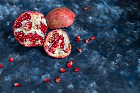 Large pomegranate broken into pieces. On a blue background under a stone. Trend 2020. Grains are scattered nearby. Copy space. Stock Photo