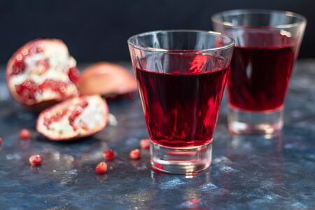 Pomegranate juice in transparent glasses. In the background are parts of a large pomegranate. On a blue background under a stone. Trend 2020. Grains are scattered nearby. Copy space.