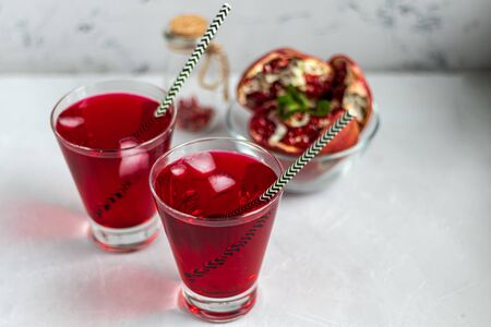Pomegranate juice in transparent glasses. On a light background under a stone. Trend 2020. Grains are scattered nearby. Copy space.