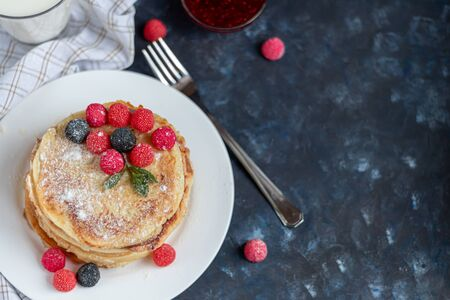 A stack of delicious pancakes with raspberries, blackberries and blueberries. On a dark stone background. Sprinkled with icing sugar and decorated with mint leaves. Copy space. Banque d'images - 138555118