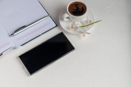 White office desk with necessary items on it. Diary with pen, Samsung phone. White cup of coffee. Top view with copy space, flat lay.