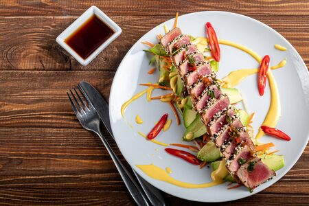 Japanese food. Tataki with tuna. Fried fish with sesame seeds and soy sauce, wasabi, lime. On a pillow of vegetables. Avocados, strips of chili peppers, carrots. On a wooden background. Copy space. Stock Photo