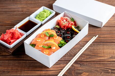 A box of sushi Nigiri, Uramaki California, Philadelphia, on a black stone plate. Sushi menu in a white transport box on a wooden background. Copy space. Stock Photo