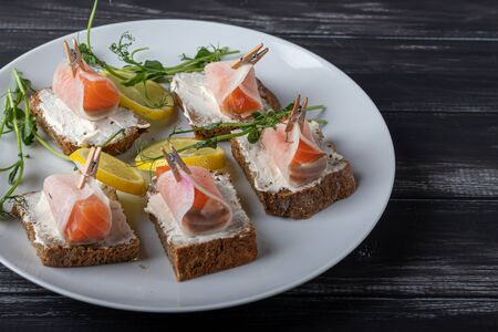 Sandwiches with salmon on dark bread, spread with cheese sauce. The meat is wrapped in a slice of daikon and fixed with a decorative clothespin. On a wooden background. Copy space