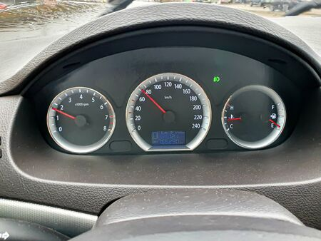 Car dashboard. Speedometer, circular tachometer, oil and fuel level, mileage. Outside the window it is raining, the wipers are visible.