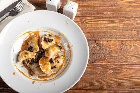 Ravioli stuffed with cottage cheese and poppy seeds. Served with poppy seeds and caramel sauce. On a large white plate. On a wooden background. Copy space