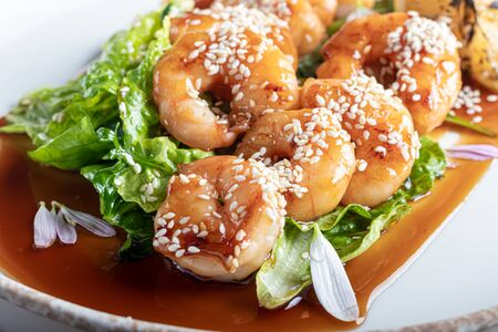 Shrimps cooked in teriyaki sauce with a slice of fried lemon on a pillow of lettuce leaves. On a white background, on a dark wooden background. Copy space