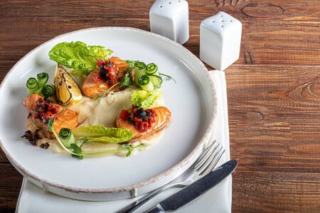 Celery and potato puree with pieces of red fish, garnished with herbs and fresh cucumbers. On a white plate with lemon slices. On a wooden table. Copy space