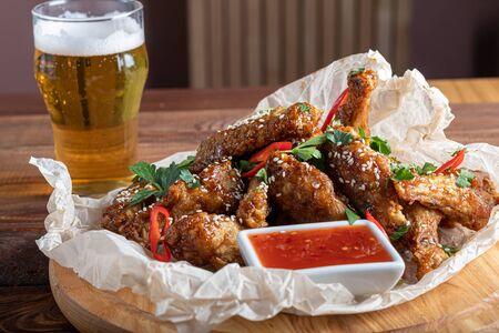 Chicken wings in soy sauce. Served for beer. Sprinkle with sesame seeds. Next to chili pepper sauce and tomatoes. On a wooden board. Copy space