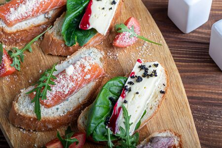 Sandwiches with red fish, beef in suvit and soft cheese. Garnished with slices of microgreen, arugula and tomatoes. On a wooden oval tray. Copy space