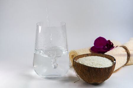 Collagen powder in half coconut. In the background, water is poured into a glass. The frame is frozen. Extra protein intake. Natural supplements for beauty and health. Collagen based plant concept.