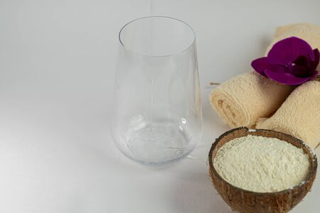 Collagen powder in half coconut. In the background, water is poured into a glass. The frame is frozen. Extra protein intake. Natural supplements for beauty and health. Collagen based plant concept. Fl 스톡 콘텐츠