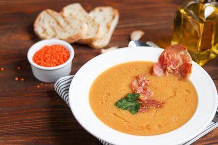 木製の背景にレンズ豆を持つ野菜スープ。刻んだチェリートマトとハーブを添えて。近くにはシアバッタの破片があります。生のうめき声を背景に。ベジタリアン料理。スペースをコピーする
