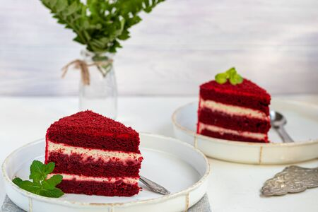 Cake Red velvet on two white plates, two servings. On a light background. Birthday, holidays, sweets. Copy space