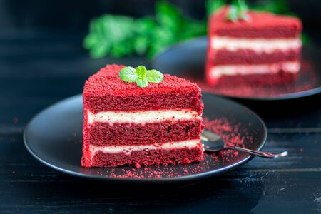 Cake Red velvet on two white plates, two servings. On a black background. Birthday, holidays, sweets. Copy space