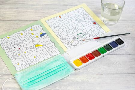 Handmade crafts. Creative activities for children on vacation and in quarantine. Coloring book with english words. Mask for protection against the virus. Children's creativity. Copy space.