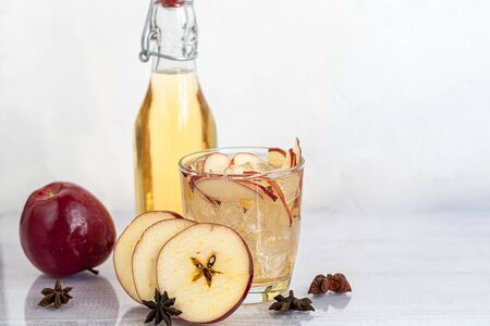 Healthy organic foods. Apple cider in a glass bowl and fresh red apples on a light background. In a glass of ice cubes and nearby cinnamon sticks. Copy space