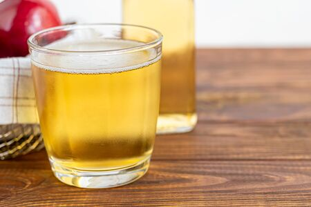 Healthy organic foods. Apple cider in a glass bowl and fresh red apples on a wooden background. In a glass of ice cubes and nearby cinnamon sticks. Copy space Standard-Bild