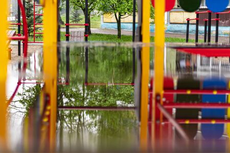 Empty swing at the playground in the rain. Children's swing in the park, wooden benches, slides, sports equipment. Empty city, quarantine. The concept of loneliness.