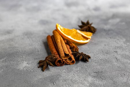 Cinnamon sticks, anise stars and nutmeg on a gray background. Near slices of chips from an orange. Useful spices that improve the taste of dishes. Copy space