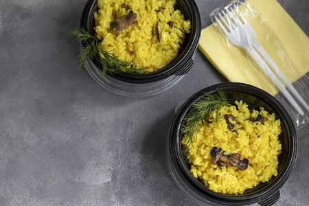 Italian risotto with champignons and parmesan. Food is delivered to your home in quarantine in disposable utensils. Rice is seasoned with turmeric and herbs. Copy space