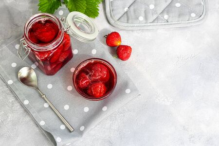 Strawberry jam in a glass jar next to fresh strawberries. On a gray background. Homemade winter fruit blanks. Selective focus. Copy space