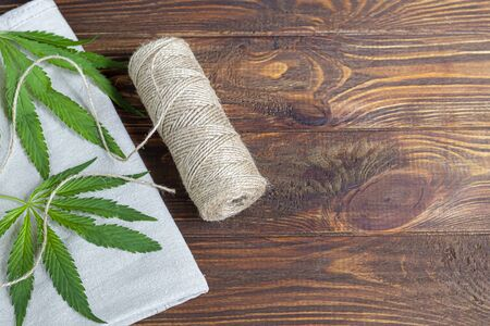 Cannabis fabric and rope on wooden background. Industrial production. Copy space