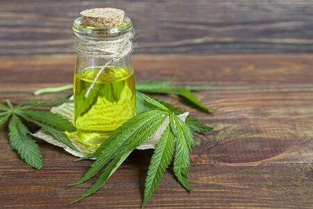 Cannabis oil in a transparent bottle and hemp leaves on a wooden background. Copy space. Фото со стока