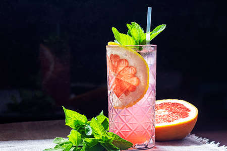 A refreshing summer cocktail with a slice of grapefruit. Alcoholic drink Paloma. Decorated with a sprig of mint and ice cubes. Foreground.